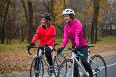 2 молодых усмехаясь женских велосипедиста при велосипеды дороги отдыхая и в парке в холодном дне осени Здоровый уклад жизни Стоковые Фотографии RF