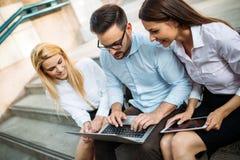3 молодых усмехаясь коллеги работая совместно на компьтер-книжке Стоковая Фотография RF