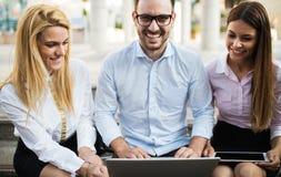 3 молодых усмехаясь коллеги работая совместно на компьтер-книжке Стоковое Изображение RF
