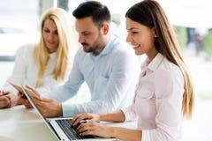 3 молодых усмехаясь коллеги работая совместно на компьтер-книжке Стоковые Изображения RF