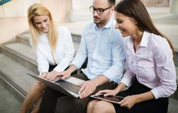 3 молодых усмехаясь коллеги работая совместно на компьтер-книжке Стоковое Фото