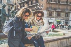 2 молодых усмехаясь туристских женщины сидят на улице города около фонтана и ищут путь на карте Стоковая Фотография RF