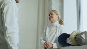 2 молодых фехтовальщика человек и женщина беседуя после ограждать турнир внутри помещения