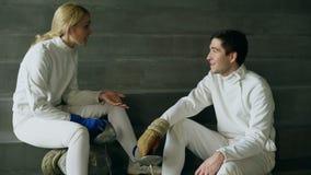 2 молодых фехтовальщика человек и женщина говоря после ограждать тренировать внутри помещения