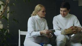 2 молодых фехтовальщика человек и конкуренция женщины наблюдая ограждая на smartphone и опыт делить после тренировать внутри поме сток-видео