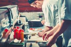 2 молодых шеф-повара в белых равномерных подготавливая сушах Стоковое фото RF