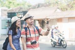 2 молодых backpackers принимая selfies используя камеру мобильных телефонов стоковая фотография