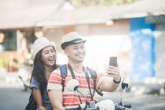 2 молодых backpackers принимая selfies используя камеру w мобильных телефонов стоковое фото rf