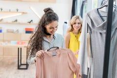 2 молодых shopaholic женщины выбирая одежды Стоковые Изображения