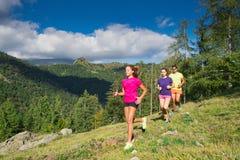 2 молодых sporty девушки и мальчик бежать совместно на траве i Стоковые Фото