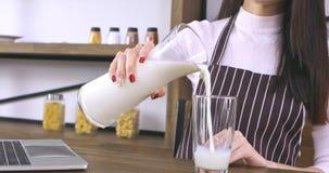 Молоко азиатской женщины лить от кувшина в стекло акции видеоматериалы