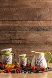 Молоко в керамическом кувшине и 2 опарниках размера с печеньями и смешивание диких ягод на деревянной предпосылке стоковые фотографии rf