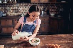 Молоко девушки лить в шар хлопьев мозоли стоковое изображение rf
