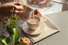 Молоко женщины лить в чашку с ароматичным чаем на таблице стоковое изображение rf