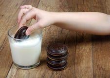 молоко печений Рука ` s детей с печеньями Стоковое Изображение RF