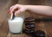 молоко печений Рука ` s детей с печеньями Стоковые Фотографии RF