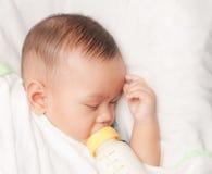 молоко удерживания мальчика бутылки младенца стоковое изображение