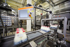 молоко фабрики транспортера бутылок обернуло Стоковое Фото