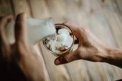 Молоко человека лить в замороженном кофе стоковое изображение
