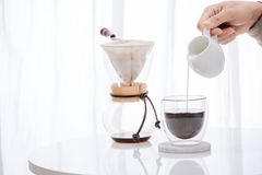 Молоко человека лить в стекло с холодным кофе brew на таблице стоковые изображения rf