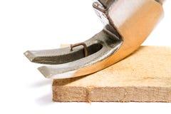 Молоток извлекает заржаветый ноготь от деревянной плиты дальше стоковая фотография