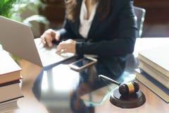 Молоток и юрист судьи работая на ноутбуке в офисе стоковые фотографии rf