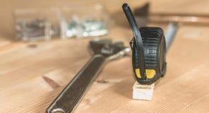 Молоток пригвождает ключ и метр клал на деревянный стойл стоковое фото