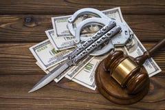 Молоток судьи; нож; наручники и доллары денег на деревянной предпосылке текстуры стоковая фотография