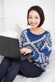 Молодая азиатская женщина используя компьтер-книжку Стоковое Фото