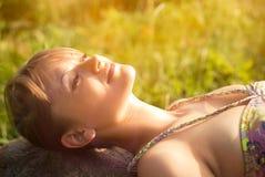 Молодая женщина лежа на камне Стоковые Изображения