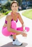 Молодая женщина отдыхая во время тренировки в парке Стоковое фото RF