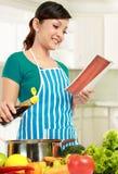Молодая женщина читая книгу рецепта Стоковые Фото