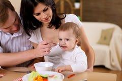 Молодая семья на дому имея еду Стоковое фото RF