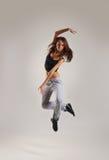 Молодой женский танцор скача в sporty одежды Стоковое Фото