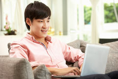 Молодой китайский человек используя компьтер-книжку пока ослабляющ Стоковая Фотография