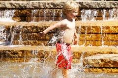Молодой мальчик играя в фонтане воды Стоковые Изображения