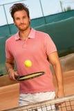 Молодой человек играя усмехаться тенниса Стоковая Фотография RF
