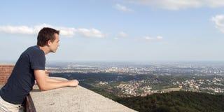 Молодой человек наслаждаясь взглядом - панорамой Стоковые Изображения