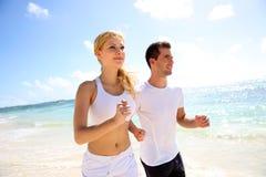 Молодые пары jogging на пляже Стоковое Изображение RF