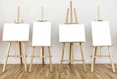 4 мольберта студии искусства с пустыми белыми рамками картины Стоковая Фотография RF
