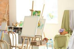 Мольберты с холстом подготовленным для крася классов в мастерской стоковое изображение rf