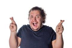 Момент смешного жирного человека ждать особенный и пересекая пальцы стоковые изображения rf