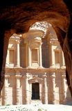 Монастырь al-Deir в горах Petra, Джордане, обрамленном утесами пещеры стоковые фотографии rf