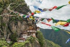Монастырь Taktsang Palphug при флаг молитве (также известный как висок гнезда тигра), Paro, Бутан Стоковые Изображения RF