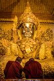 2 монаха моля золотой статуей Будды, Мьянмой (Бирма) стоковое фото