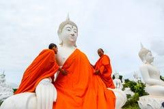 Монахи одевая одно из белого изображения Будды с робами стоковые фото
