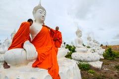 Монахи одевая одно из белого изображения Будды с робами стоковые фотографии rf
