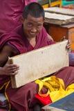 Монах читая и изучая традиционную книгу Стоковое Изображение RF