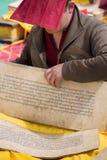 Монах читая и изучая традиционную книгу Стоковое Фото
