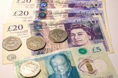 Монетка английского фунта на кредитках английского фунта Стоковое фото RF